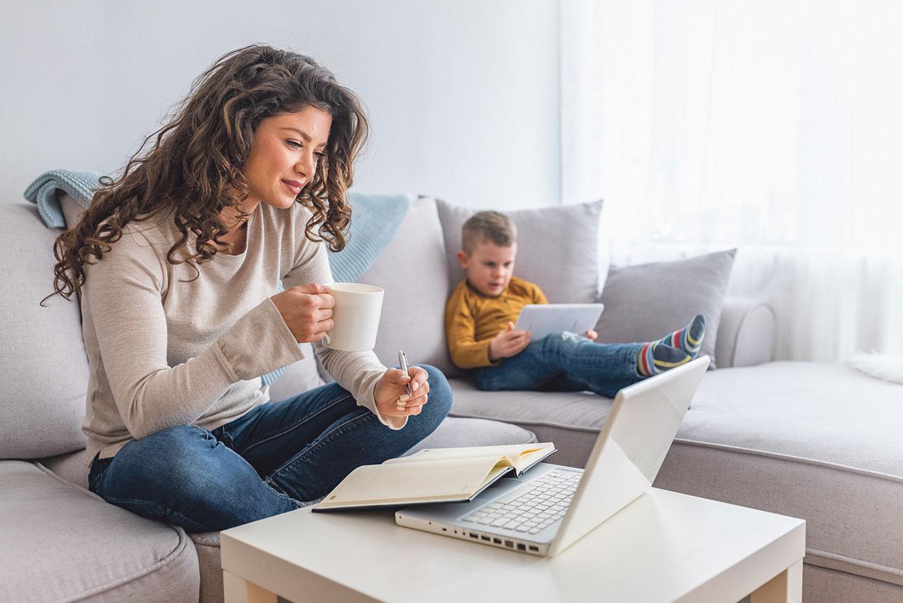 Ein Kind sitzt mit Tablet auf der Couch, die Mutter daneben mit einem Laptop. Thema: Digitalisierung in allen Lebensbereichen