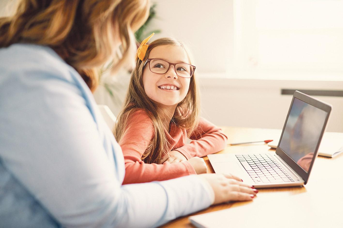 Ein Mädchen sitzt neben einer Frau und lernt am Laptop.