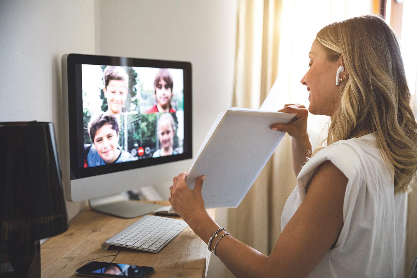 Eine Lehrerin im Videocall mit Schülern