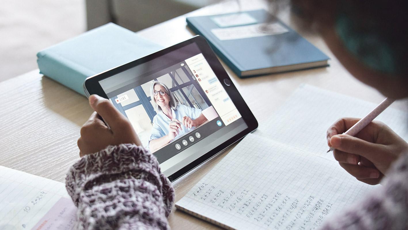 Schülerin nimmt an Online-Unterricht mithilfe eines Tablets teil.