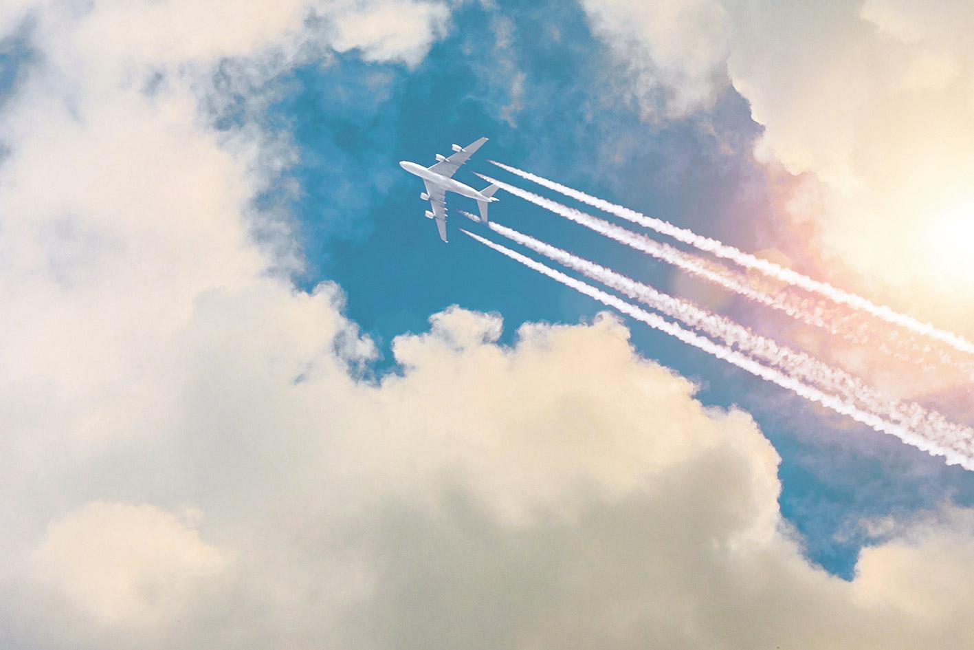 Ein Flugzeug hinterlässt Kondensstreifen an einem wolkigen Himmel.