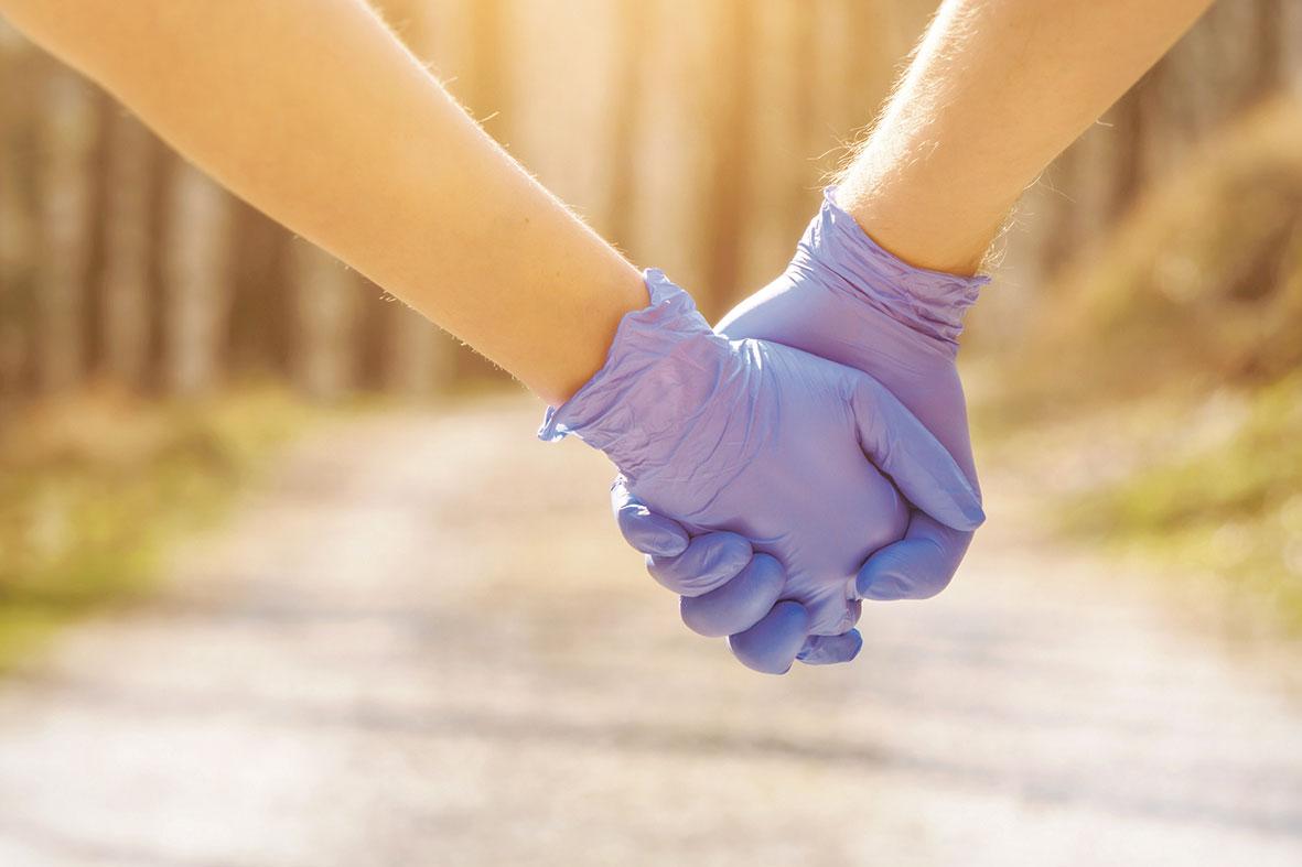 Zwei Hände in Gummihandschuhen halten sich fest. Thema: Lockdown während der Corona-Pandemie
