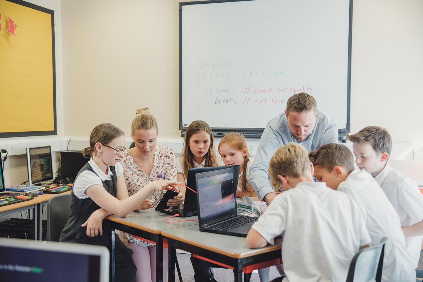Eine Gruppe von Schülern arbeitet an Laptops.