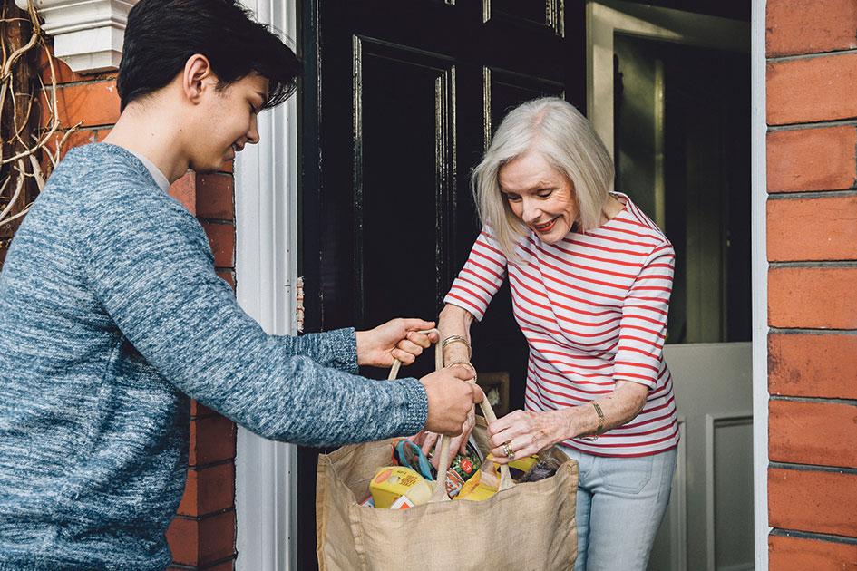 Junger Mann übergibt einer älteren Frau eine Einkaufstasche. Thema: Nachbarschaftshilfe und Betrugsmaschen während der Corona-Pandemie