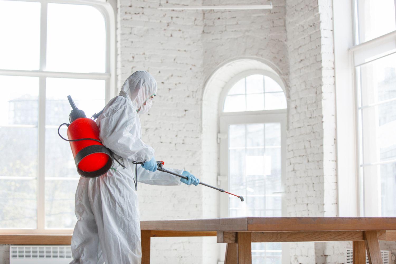 Eine Person im Schutzanzug desinfiziert einen Raum.