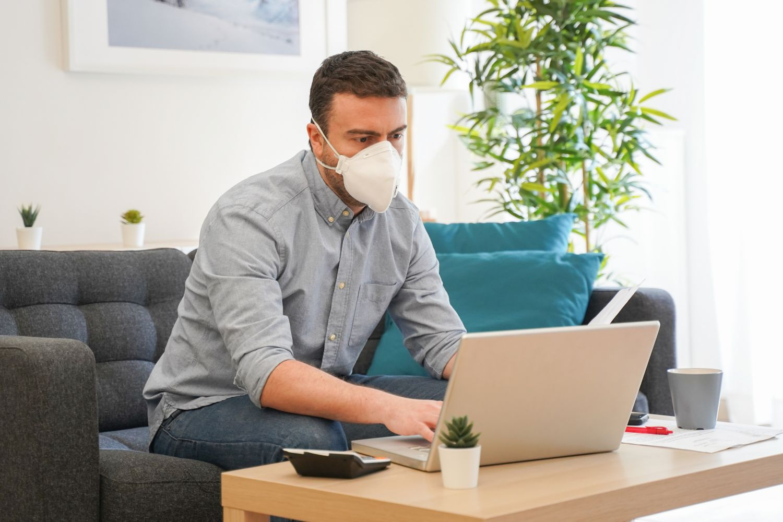 Mann im Home Office mit Gesichtsmaske: Symbolbild für Sicherheit