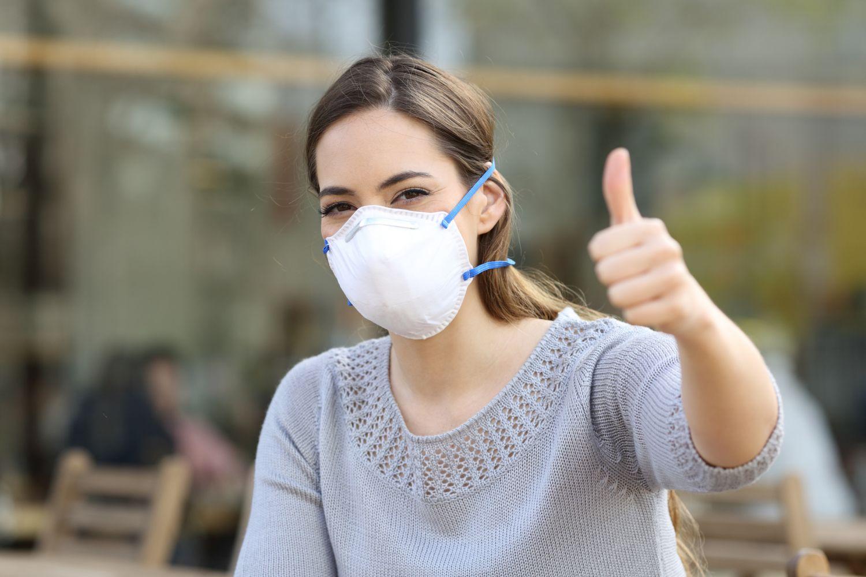 Junge Frau mit Nase-Mund-Bedeckung freut sich und hält den Daumen nach oben. Thema: Umdenken in Unternehmen
