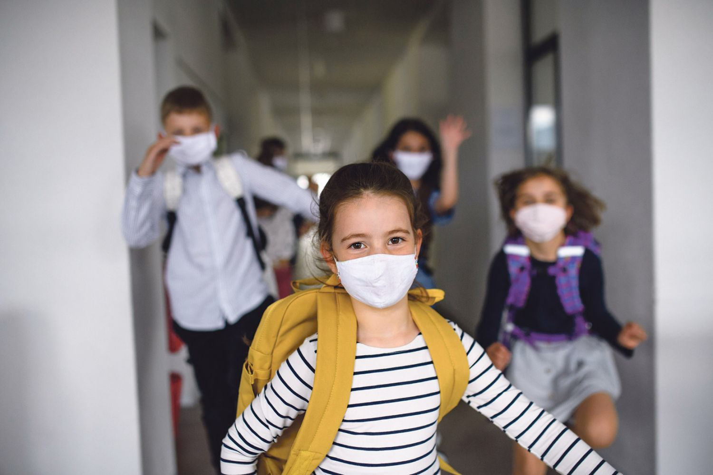Schülerinnen und Schüler mit Maske auf dem Schulflur