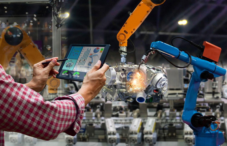 Produktionsmitarbeiter bedient mit einem Tablet eine Maschine.